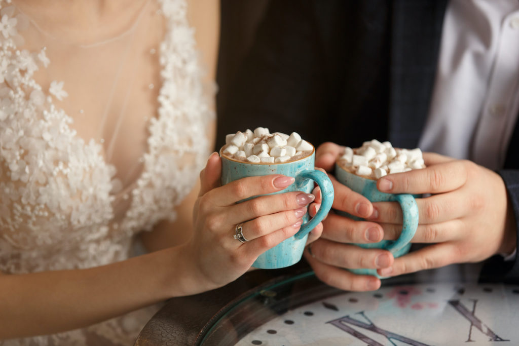Wedding in winter weather. Bride and groom holding cups of coffee with marshmallows.
